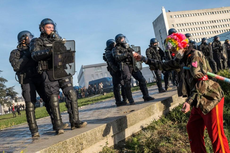 Un clown essai de donner un coeur en papier à un gendarme pour le coller sur son bouclier.